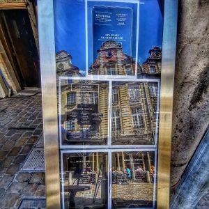 Photo de la carte du capone à arras avec les facades des places qui se reflètent sur la vitre