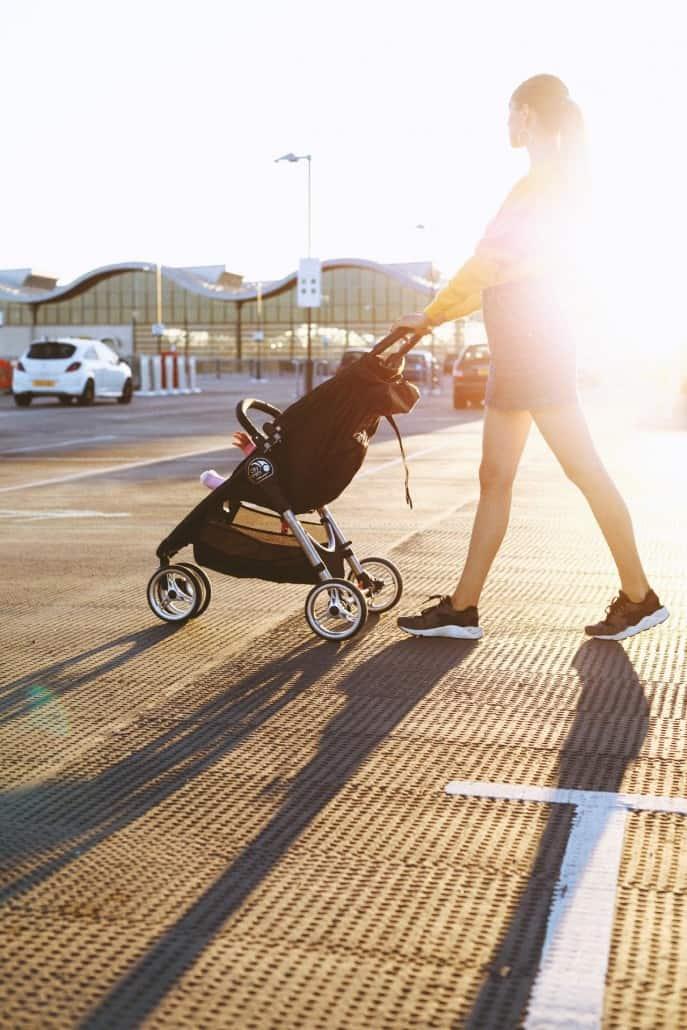 Une maman pousse un poussette landau