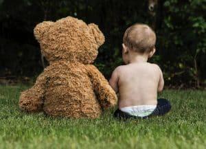 un bébé parle avec un ours en peluche